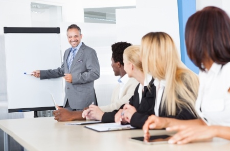 21328368 - businesspeople looking at businessman explaining in presentation